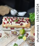 Small photo of Raspberry and pistachio meringue roulade with lemon