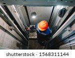 Small photo of Elevator operator in the Elevator shaft makes repairs
