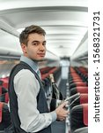 Small photo of Waist up of air steward standing in empty plane stock photo