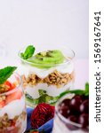 Small photo of vertical crop image of dessert with strawberries, cherries, kiwi, cream, granola and mint. trifle concept