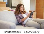 woman relaxing on sofa with... | Shutterstock . vector #156929879