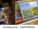 London, UK - Circa November 2019: Holiday brochures and travel guides seen stacked within a retail outlet bookshelf. Various designs, artworks can be seen which are free to the public. - stock photo