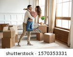 Small photo of Happy young husband lifting excited wife celebrating moving day with cardboard boxes, proud overjoyed family couple first time home buyers renters owners having fun enjoy relocation, mortgage concept