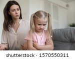 Small photo of Angry young adult mom scold stubborn fussy upset little kid daughter sulking sit on sofa ignore parent, single mother shout at unhappy preschool difficult child girl punish for bad behavior at home
