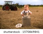 Small photo of An adorably Bavarian baby boy standing in a milk churn laughing happily. In the background a tractor is turning the hay the milk churn in standing on.