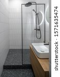 Small photo of Stylish luminous bathroom with tiled white walls and textured dark gray floor. There is a black shower, glass partition, round mirror with backlight, wooden stand with drawers and a light sink.