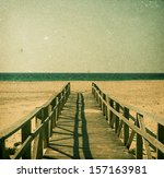 Sand beach of Tarifa, Andalusia in grunge and retro style. Pier on the foreground - stock photo