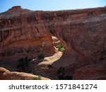 Hiking to famous Partition Arch, two round holes in massive red rock, Arches National Park, Utah