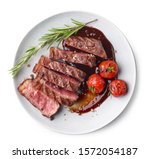 Grilled sliced Beef Steak with tomatoes and rosemary on a plate Isolated on white background top view