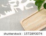 Small photo of A blank wooden tray neatly arranging on linen table cloth, with the space show sunlight and beautiful leaves shadow. Background with copy space for natural and minimal products. Soft and calm concept