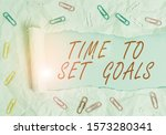 Small photo of Text sign showing Time To Set Goals. Conceptual photo Desired Objective Wanted to accomplish in the future Paper clip and torn cardboard placed above a plain pastel table backdrop.