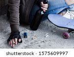 Small photo of Closeup female hands in fingerless black gloves are holding smoldering cigarette and bottle with beer. Homeless teenage girl is sitting on floor in abandoned building. Dregs of society concept.