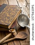 kitchen tools with cookbook on wooden table - stock photo