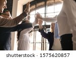 Small photo of Overjoyed older and younger teammates joining hands in air, giving high five, celebrating shared company success in business meeting. Happy diverse colleagues coming to common decision, showing unity.