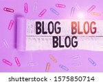 Small photo of Handwriting text Blog Blog Blog. Concept meaning Internet blogging trend modern virtual communication Paper clip and torn cardboard placed above a wooden classic table backdrop.