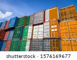 The national flag of Ireland on a large number of metal containers for storing goods stacked in rows on top of each other. Conception of storage of goods by importers, exporters