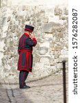 Small photo of London - September 05 2019: Yeoman Warder on his cellphone inside of the Tower of London, London September 05, 2019