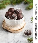 Small photo of Winter dessert, healthy sugarfree peanut butter truffles covered by dark chocolate and coconut shred, christmas and new year background, fir tree branches, wooden plate, white background
