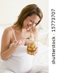 pregnant woman in bed eating... | Shutterstock . vector #15773707