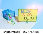Small photo of Writing note showing Blog Blog Blog. Business photo showcasing Internet blogging trend modern virtual communication Trash bin crumpled paper clothespin reminder office supplies.