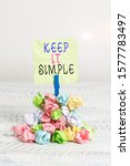 Small photo of Writing note showing Keep It Simple. Business photo showcasing Easy to toss around Understandable Generic terminology Reminder pile colored crumpled paper clothespin wooden space.