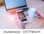 Small photo of Writing note showing Let S Work Together. Business photo showcasing Unite and Join Forces to Achieve a Common Goal woman with laptop smartphone and office supplies technology.