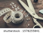 Small photo of Tailoring scissors, measuring tape, thimble, including pins, chalk. Human body measurements are written on a wooden board.