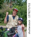 Small photo of MINNEAPOLIS, MINNESOTA / USA - JULY 09, 2017: Infamous photographer Steve Skjold celebrates the moment with his granddaughter age 10 during a family bicycle trip.