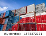 The national flag of Chile on a large number of metal containers for storing goods stacked in rows on top of each other. Conception of storage of goods by importers, exporters