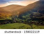 sunrise in small village at the foot of a  mountain - stock photo