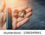 Small photo of Vape pod system or pod mod with changeable cartridges close up in male hand.
