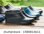 Small photo of Old rubber boots of a big family stand on the wooden floor of a country house porch lit by summer sun with green grass on the background. Short rubber country goloshes
