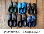 Small photo of Six pairs of old rubber boots of a big family stand on the wooden floor. Short rubber country goloshes. View from above