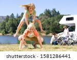 Children playing leapfrog in countryside on motor home vacation - stock photo