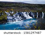 Icelandic waterfalls with low shutterspeed. Beautifull green background on a cloudy day