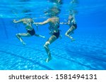 Girls team synchronized dance action underwater blue water outdoors unrecognizable swimming pool.