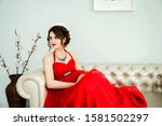 Attractive girl with red lipstick and massive jewelry with red stones in a red  poofy dress with a beautiful hairstyle sits on a satin white sofa waiting for the start of the holiday.