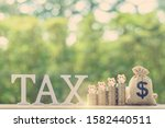 Small photo of Tax on savings interest / deposit tax refund, financial concept : Piggybanks on stacks of coins and US dollar bag, depict planning for personal allowance / earning tax-free or exempt from paying tax