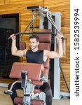 Small photo of Handsome man exercising on lat pull down machine