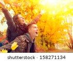 happy couple in autumn park.... | Shutterstock . vector #158271134