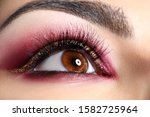 Close-up of cozy autumn makeup. Adorable woman with luxury glossy shadows and beautiful poofy eyelashes. Golden glitter on eyes. Fashion and beauty concept