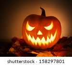 Stock photo halloween pumpkin with leafs on orange background 158297801
