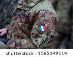 Details with the uniform and the flag on it of an Italian soldier taking part at the Romanian National Day military parade.