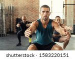 Young Man Exercising With Squa...