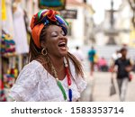 Small photo of Happy Brazilian woman of African descent dressed in traditional Baiana costumes in the Historic Center of Salvador da Bahia, Brazil.