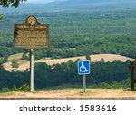 Handicap sign with wheelchair symbol next to marker in FDR State Park, Georgia