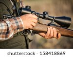 Small photo of hunter holding a rifle