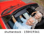 High angle view of cheerful mature man having a ride with his wife in red convertible - stock photo
