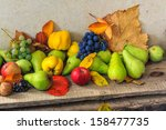 autumnal fruit still life with apples, pears, quince, grapes nuts and leaves on wooden base - stock photo