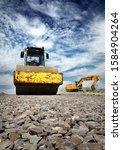 Small photo of Excavator and steamroller on gravel road construction